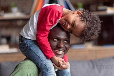african american father and son spending time together at home