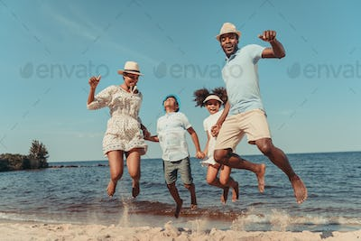 happy african american family holding hands and jumping uphigh on beach