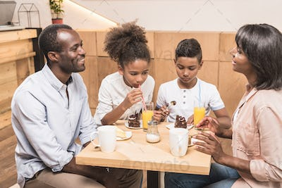 adorable african-american family eating desserts in cafe