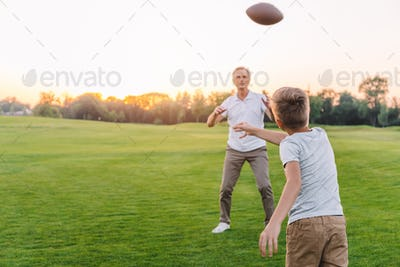 back view of little boy throwing rugby ball while playing american football with grandfather