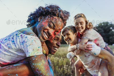 happy young multiethnic couples piggybacking at holi festival