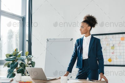 beautiful serious african american businesswoman looking away in office