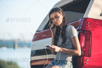 young woman listening music with earphones while leaning back on car