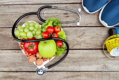 top view of stethoscope, organic vegetables and fruits and measuring tape on wooden surface, healthy