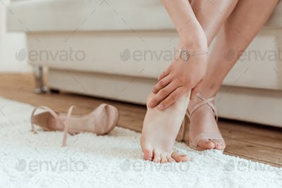 cropped shot of tired woman taking shoes off and holding leg