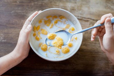 cropped shot of child eating corn flakes for breakfast