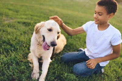 happy african american teenager playing with golden retriever dog