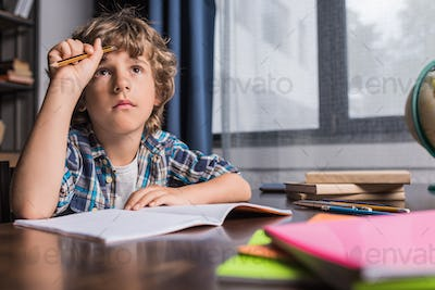 portrait of thoughtful little boy looking away while doing homework at home