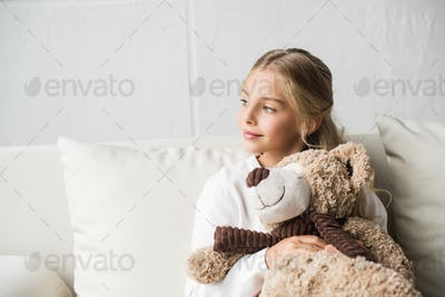 happy child hugging teddy bear while sitting on sofa at home