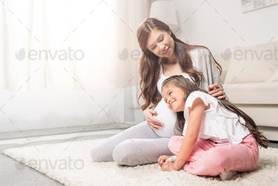 Pregnant woman with her little daughter listening to her belly.