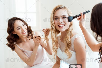 beautiful young bride getting makeup before wedding and looking at camera