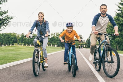 smiling parents and son riding bicycles together in park