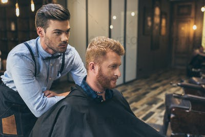 Stylish young barber standing behind customer that sitting in barber shop