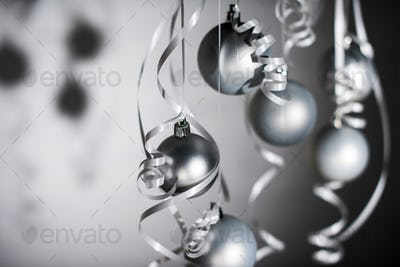 selective focus of grey christmas balls on ribbons isolated on grey