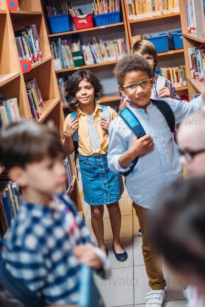 cute little kids looking for books in school library