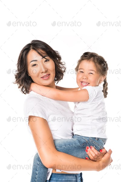 smiling asian mother hold in hands her adorable daughter, isolated on white