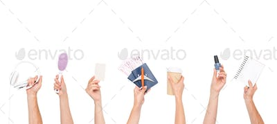 cropped shot of human hands holding headphones, hairbrush, blank card, passports with tickets and