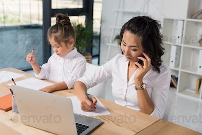 asian businesswoman working while her adorable daughter drawing behind in modern office