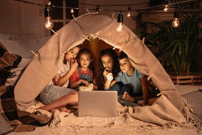 little multiethnic kids sitting tent and watching film together on laptop