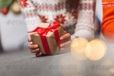 close-up partial view of young woman holding christmas present
