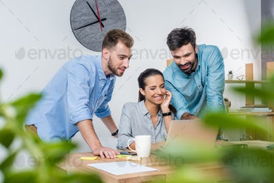 group of young business colleagues working with laptop in office together