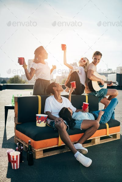 happy group of young happy friends having party on roof at sunset