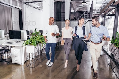 confident young smiling multiethnic business colleagues walking together in office