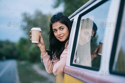 female traveler with disposable cup of coffee sitting in retro minivan