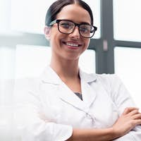Beautiful young scientist in eyeglasses standing with crossed arms and smiling at camera