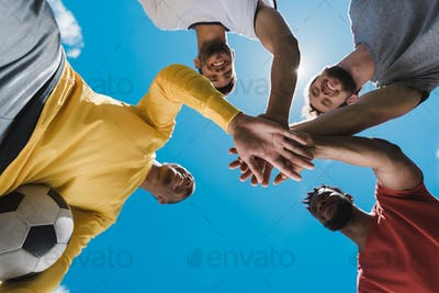Bottom view of multiethnic soccer team holding hands together before game