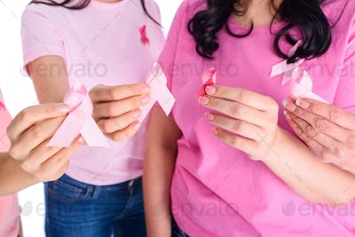 cropped shot of women in pink t-shirts holding breast cancer awareness ribbon