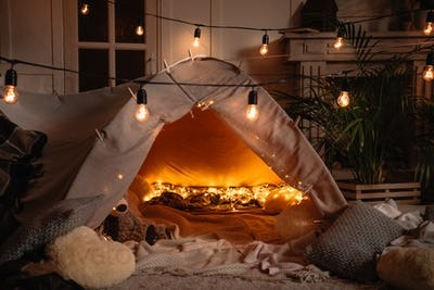handmade tent with blankets, pillows, toys and lights in room