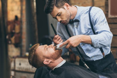 Male barber trimming customers beard in barber shop