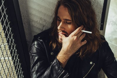 Pensive bearded long haired man in leather jacket smoking cigarette and looking away