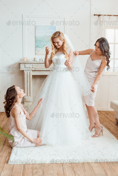 beautiful young bride with bridesmaids preparing for ceremony