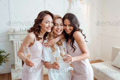 bride with bridesmaids embracing and toasting with champagne