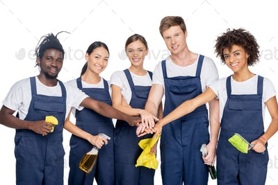 group of young multiethnic cleaners with various cleaning supplies holding hands together isolated