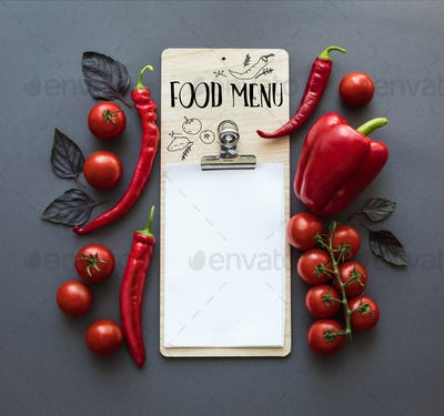 top view of various red peppers, ripe cherry tomatoes, basil leaves and blank paper sheet isolated