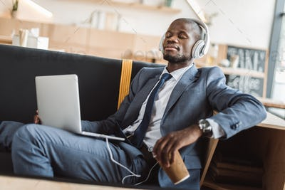 african american businessman sitting with disposable cup of coffee and listening music with