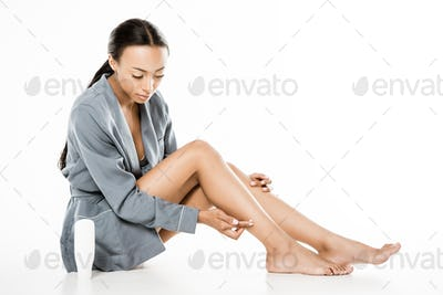 african american woman applying body cream on legs isolated on white