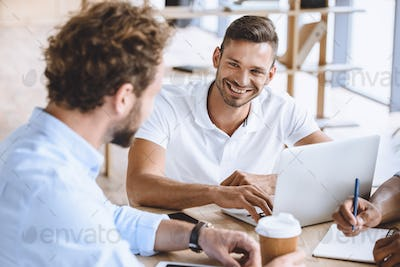 portrait of smiling businessman with laptop on meeting with coworkers in office