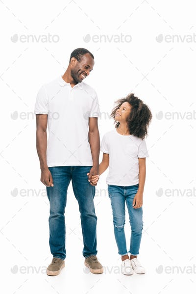 beautiful happy african american father and daughter holding hands and smiling each other isolated