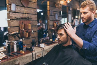 Handsome bearded man is getting hairstyle by hairdresser at the barber shop