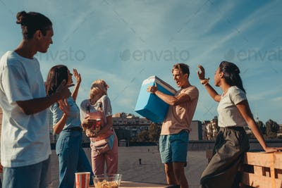 group of young friends with fridge container of beer on roof