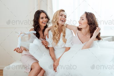 happy bride with bridesmaids holding wedding dress while sitting on sofa