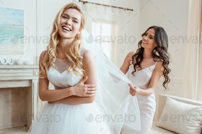 happy beautiful bridesmaid preparing laughing bride for wedding ceremony