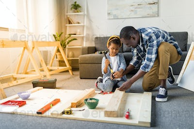 adorable african american father and son doing renovation