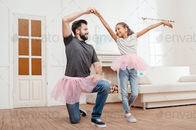 multicultural father and daughter in pink tutu tulle skirts dancing at home