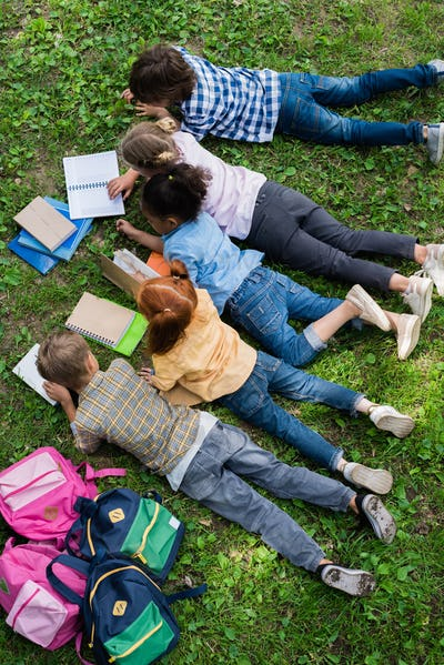 top view of cute little kids reading books while lying on grass in park