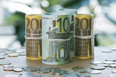 selective focus of euro banknotes in rolls with rubber bands and coins on table